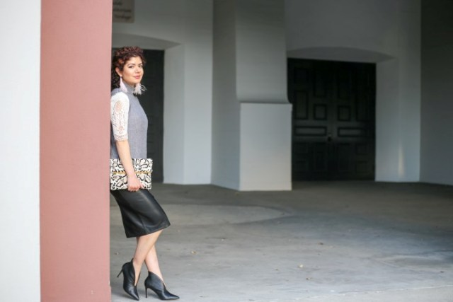 With white blouse, black leather skirt, printed clutch and ankle boots