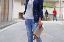 With white loose top, light blue jeans, beige leather clutch and golden shoes