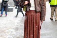 With white shirt, fur jacket, green bag and gray ankle boots