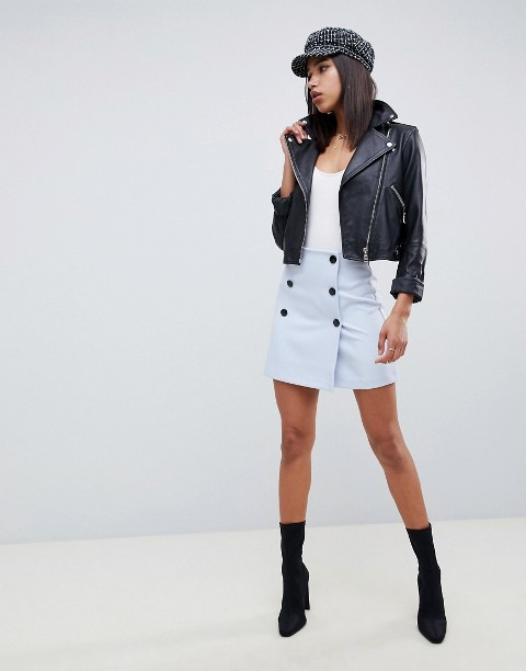 With white t-shirt, black leather jacket, cap and sock boots
