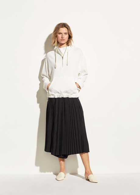 With white t-shirt, black pleated midi skirt and white mules