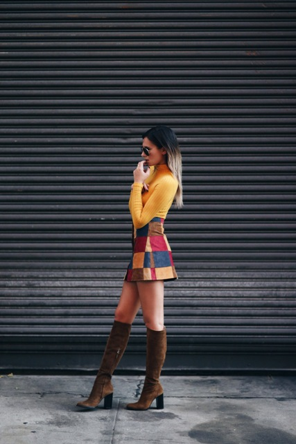 With yellow turtleneck and brown suede high boots