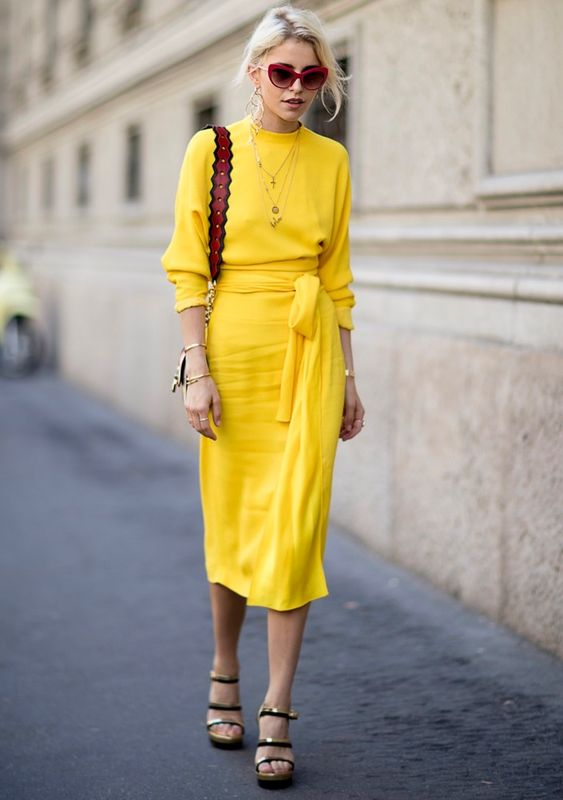 a bold spring look with a mid pencil skirt, a yellow long sleeve top, strappy platform shoes