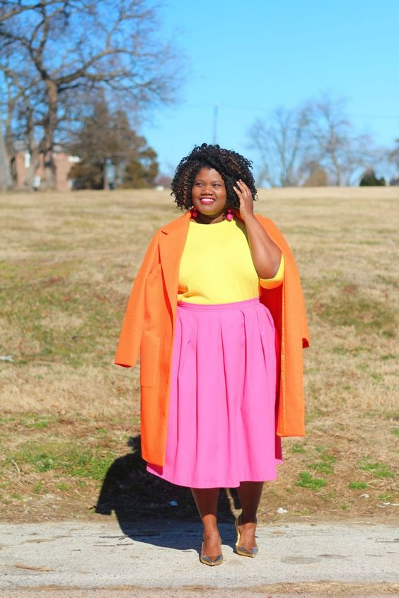 a color block outfit with a yellow top, a pink pleated midi, an orange coat and metallic shoes