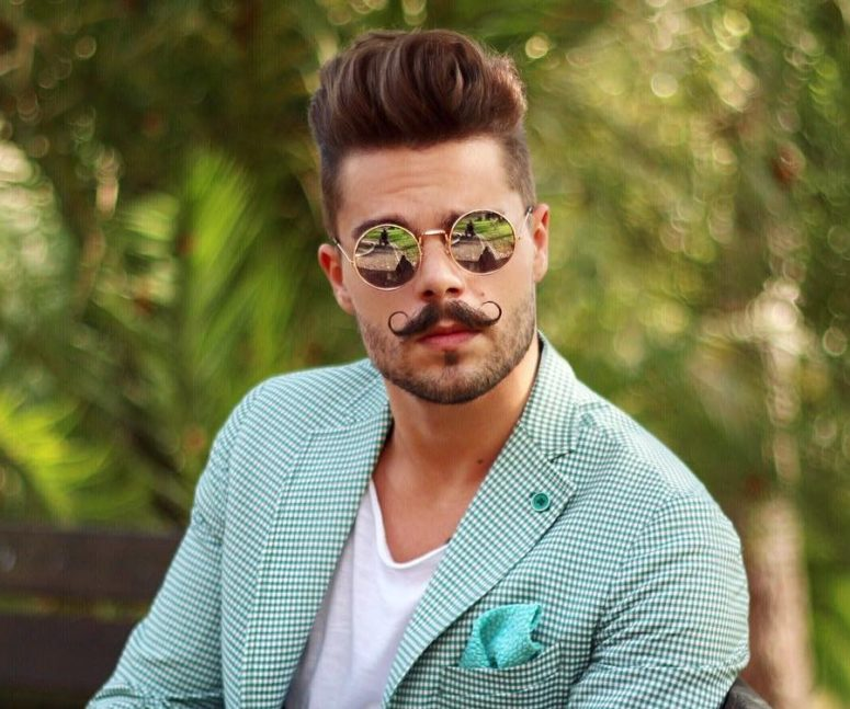 a textured pompadour and a waxed mustache create a dapper gentleman look
