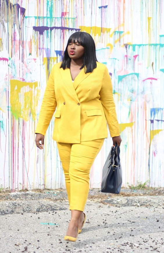 a bright yellow pantsuit with cropped pants, a white top, matching shoes and a black bag