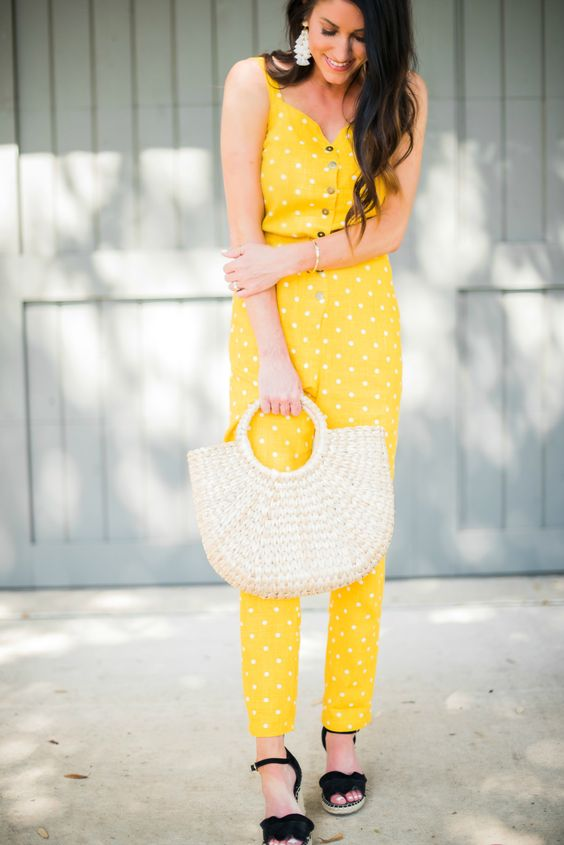 a retro-inspired yellow jumpsuit with a polka dot print, black shoes, a woven bag and statement earrings