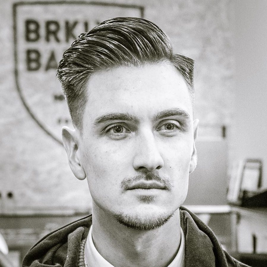 a side part haircut features a part for over to one side and a high fade, add pomade
