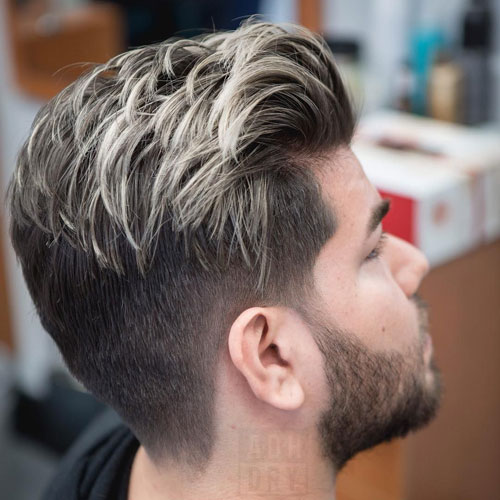 low taper fade and thick textured brush back is stylishly accented with blonde streaks