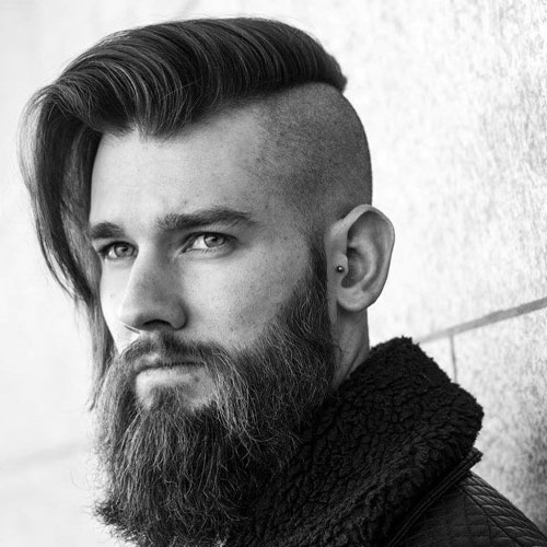 shaved sides and a long comb over plus a beard make up an ultra modern look