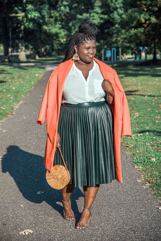 a white shirt, a dark green pleated midi leather skirt, leopard shoes and a coral coat