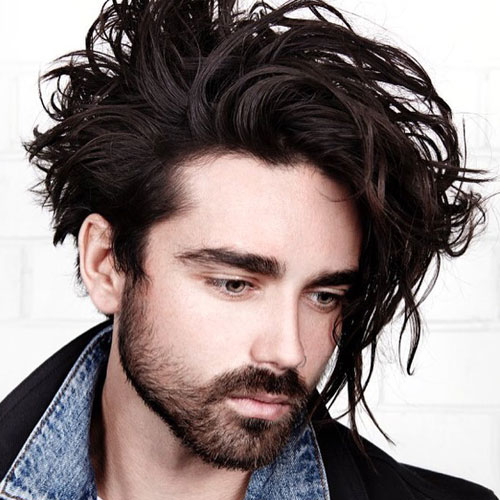 messy medium length hair with a texture and a beard create a very relaxed look