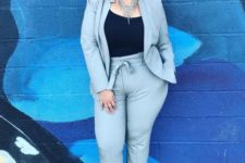 05 a grey suit with high waisted pants, a black top, neon pink shoes and a statement necklace
