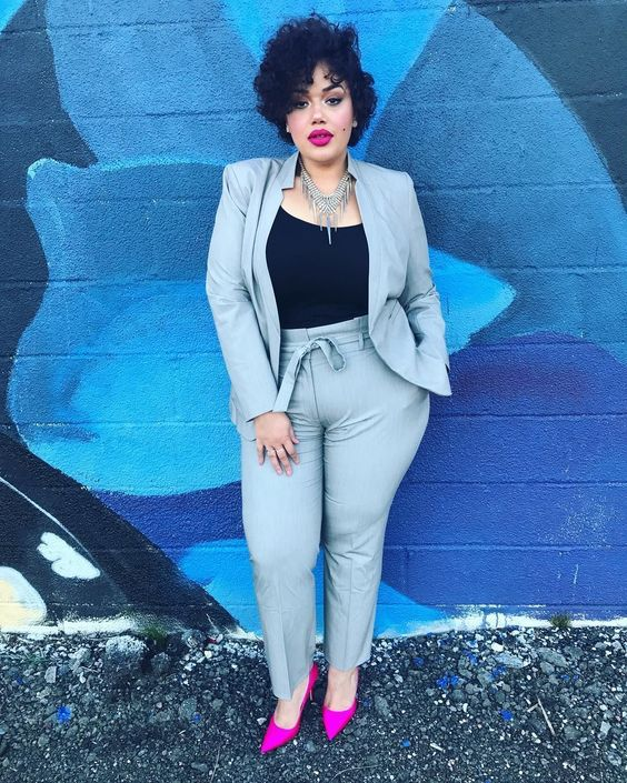a grey suit with high waisted pants, a black top, neon pink shoes and a statement necklace