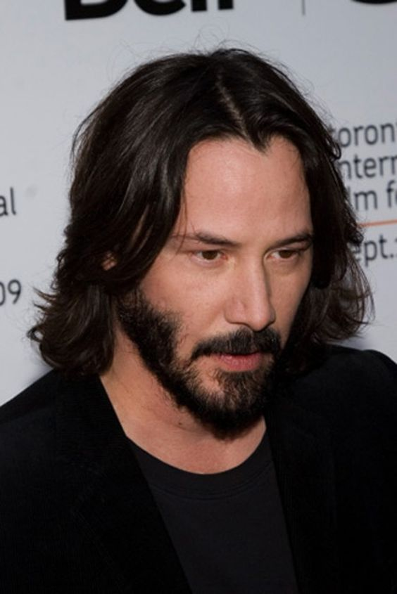 a long layered haircut with waves and a beard looks chic, proved by Keanu Reeves