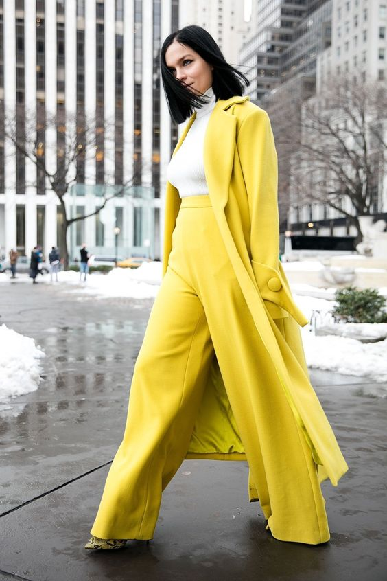 yellow wideleg pants, a white turtleneck, a yellow coat and snake print shoes