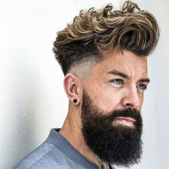 a long and super wavy quiff with faded sides, much volume and blonde highlights