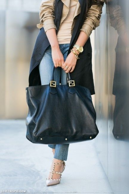 a tan shirt, a long sleeveless coat, blue jeans, studded heels and a large black tote