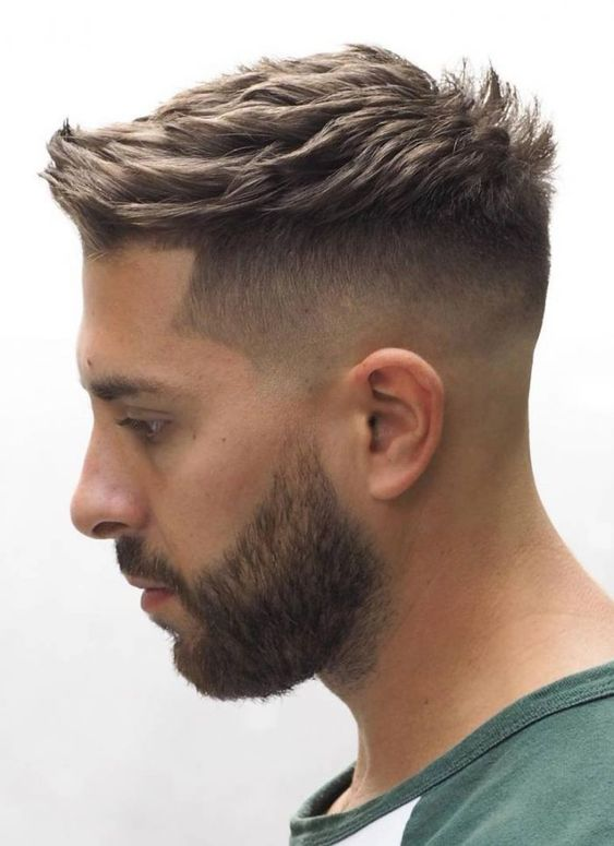 a high and tight haircut with faded sides and a curvy top plus s beard looks chic