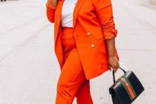 07 an orange pantsuit, a white tee, black heels and a small black and orange bag