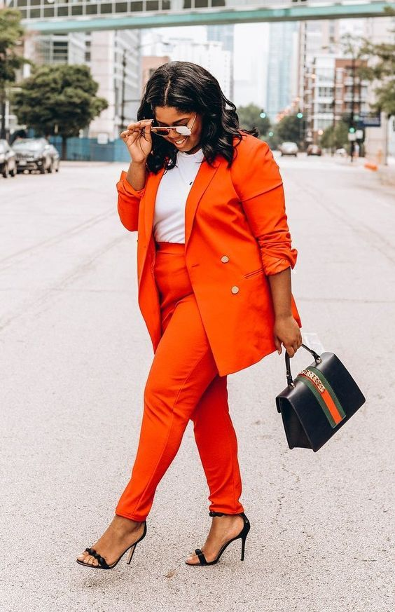 an orange pantsuit, a white tee, black heels and a small black and orange bag