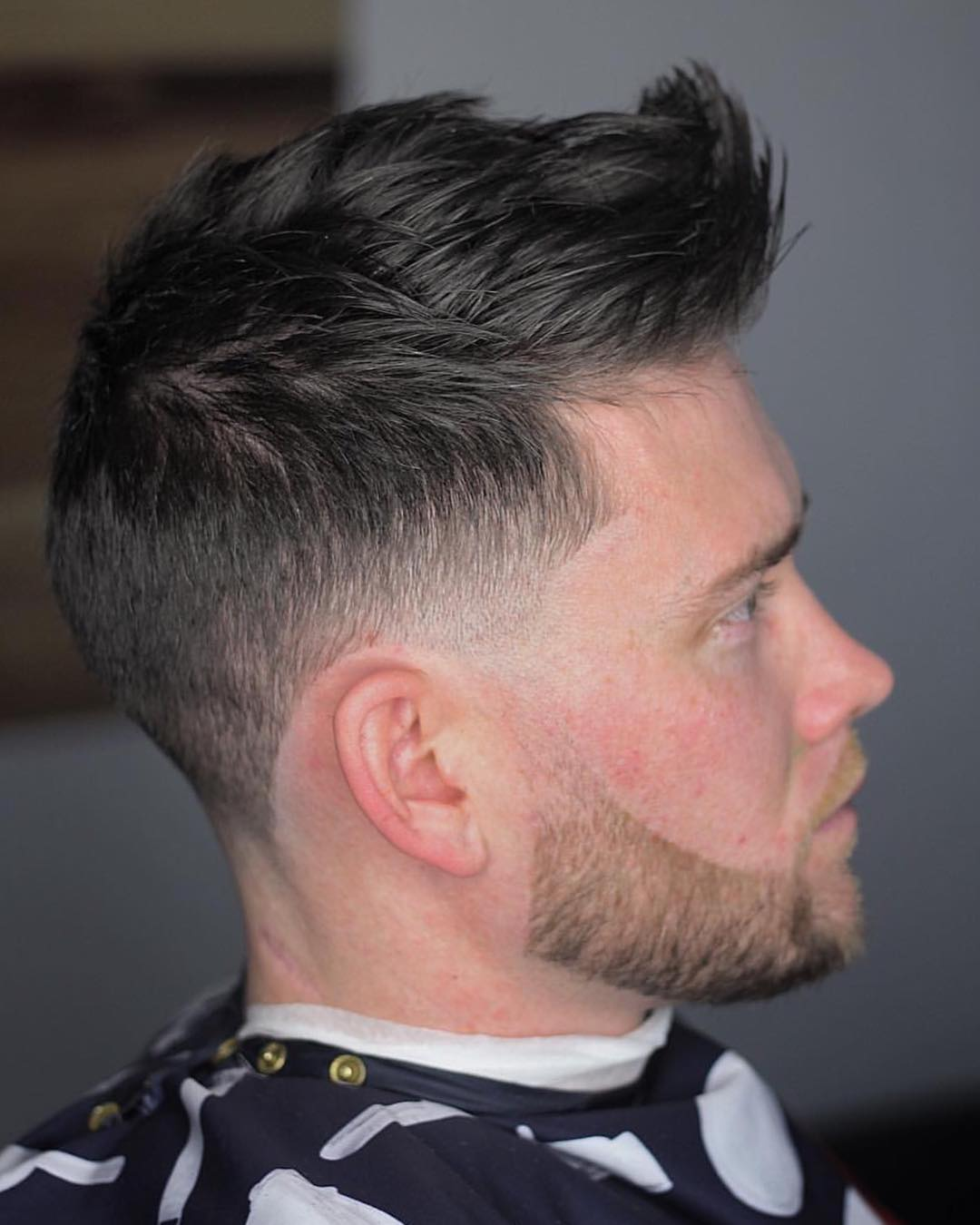 a classic faux hawk is combined with some well trimmed facial hair for unique style