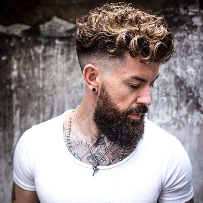 a curly undercut haircut with a high skin fade that creates a sharp contrast with curly hair