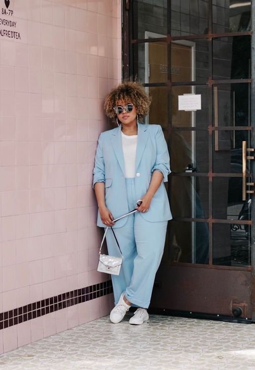 a pastel blue pantsuit, a white tee, white sneakers and a silver bag for a spring work outfit
