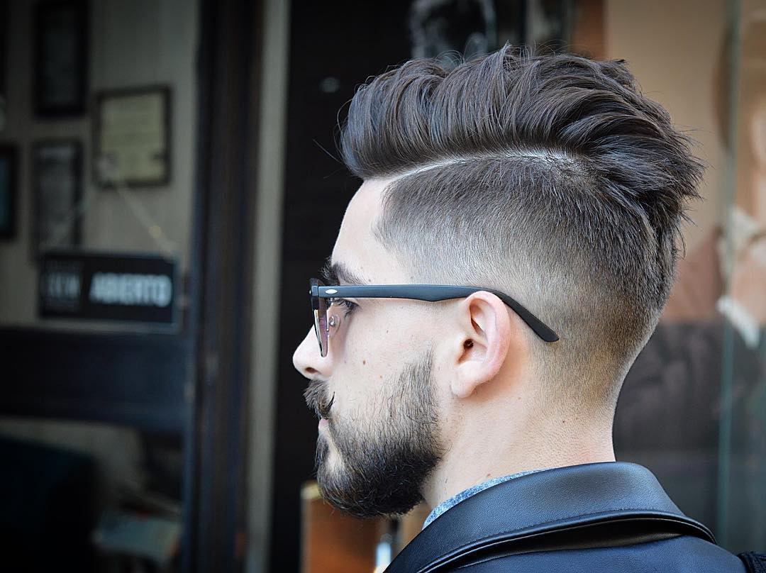 a cool messy pompadour undercut haircut styled up and a beard for a statement look