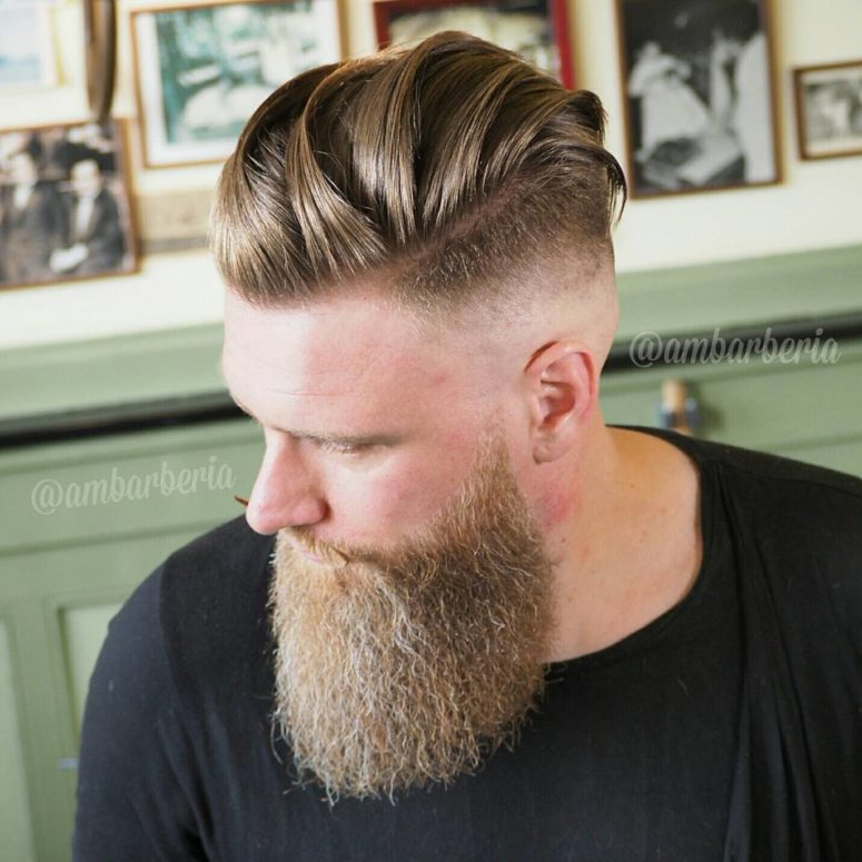 a faded undercut haircut with long hair styled back and to the side plus a trendy beard