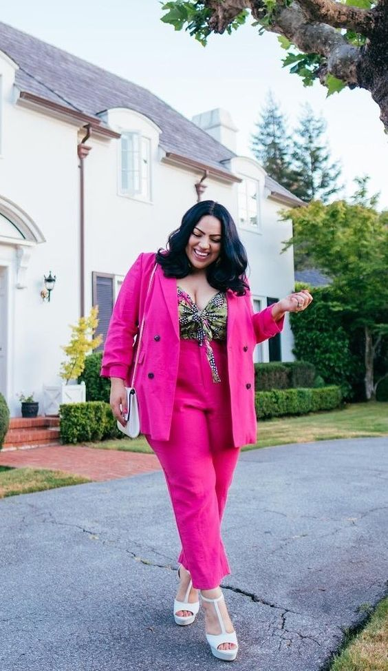 a hot pink pantsuit with a colorful printed top, white platform shoes and a white bag