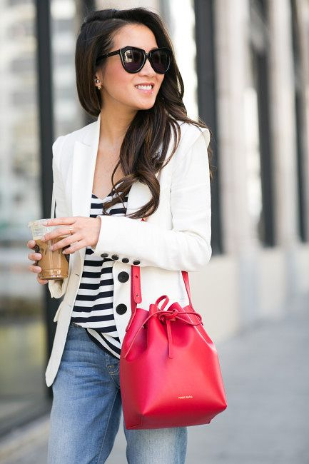 a comfy look with a striped top, blue jeans, a white blazer and a red bucket bag
