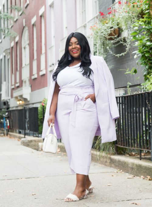 a lilac suit with a long blazer, a white top, white fur sliders and a small white bag