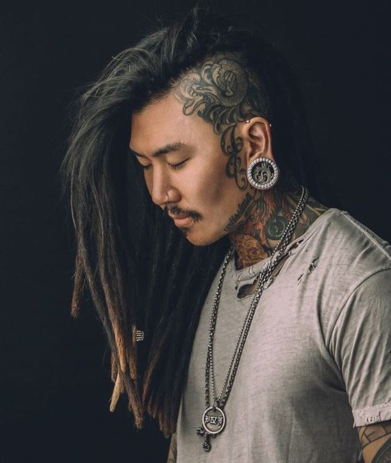 long dreadlocks with a shaved side, which is tattooed, features a bold edge