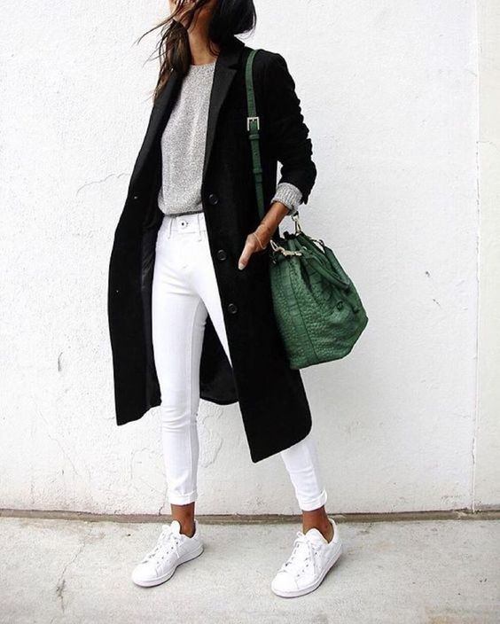 a grey long sleeve, white jeans, white sneakers, a black coat and a green bucket bag