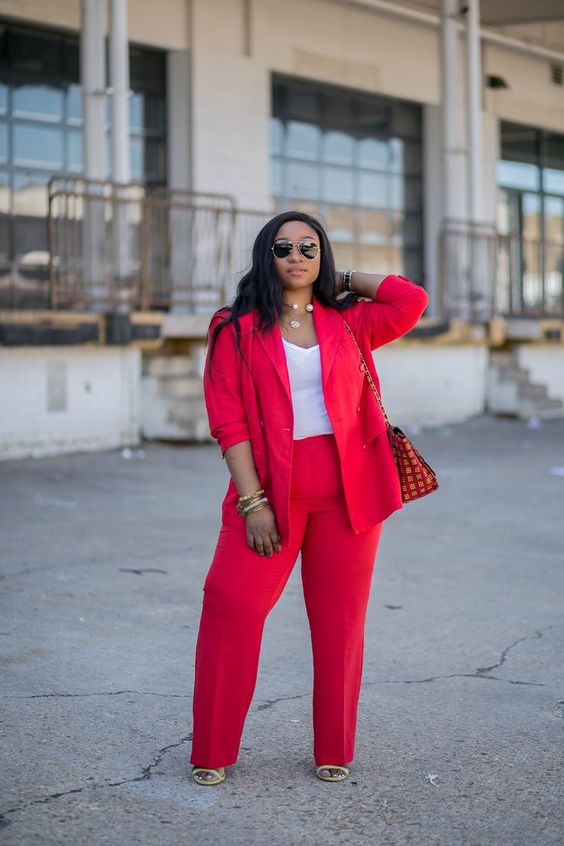 a hot red pantsuit with a white top, layered necklaces, nude shoes and a printed bag