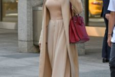 13 Angelina Jolie wearing a relaxed beige look with a tee, a skirt, a trench, and heels