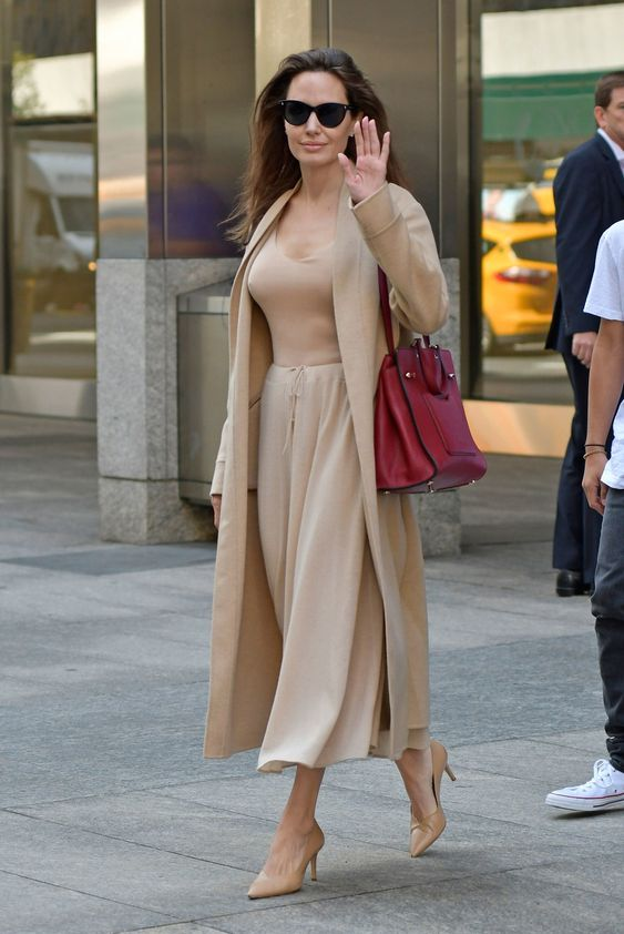 Angelina Jolie wearing a relaxed beige look with a tee, a skirt, a trench, and heels