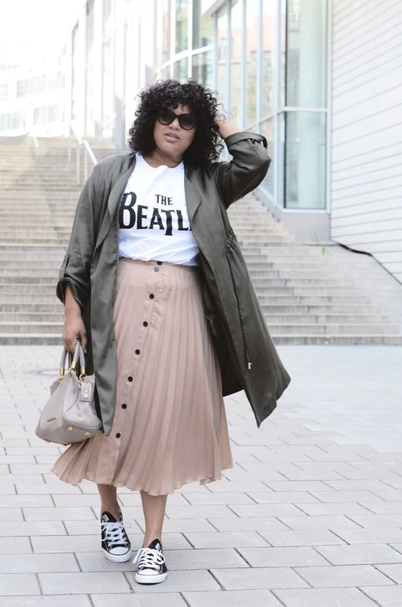 a nude button up midi skirt, a printed tee, a dark green trench and black sneakers