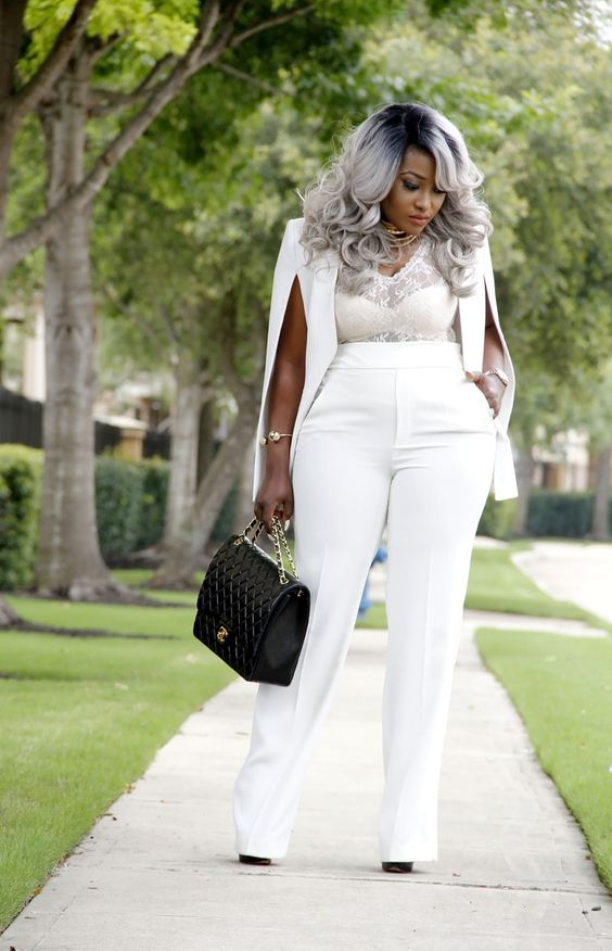 a trendy white pantsuit with a cape, a white lace top, black heels and a black bag