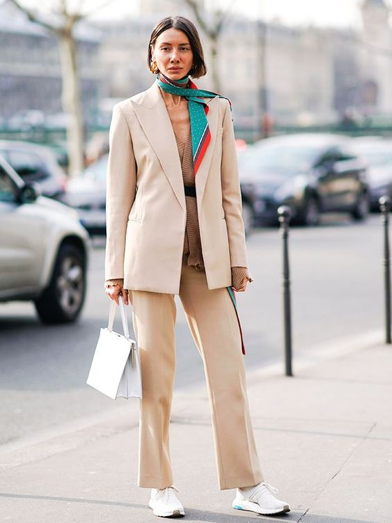 a beige outfit with a suit, a crochet top, a bold scarf and trainers