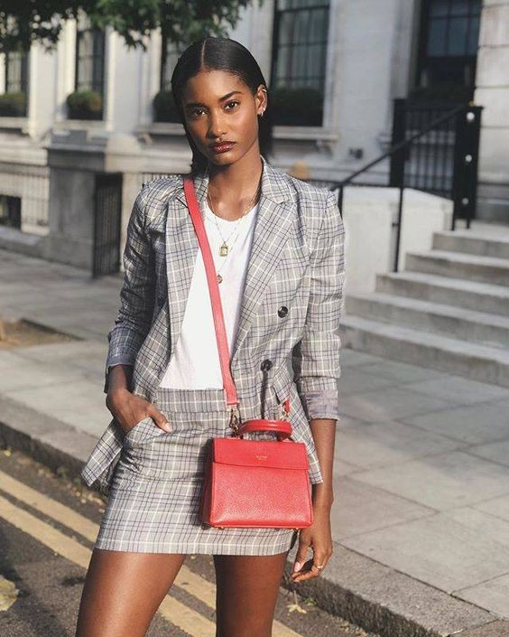 a grey checked suit with a mini skirt with pockets, a white top and a red crossbody