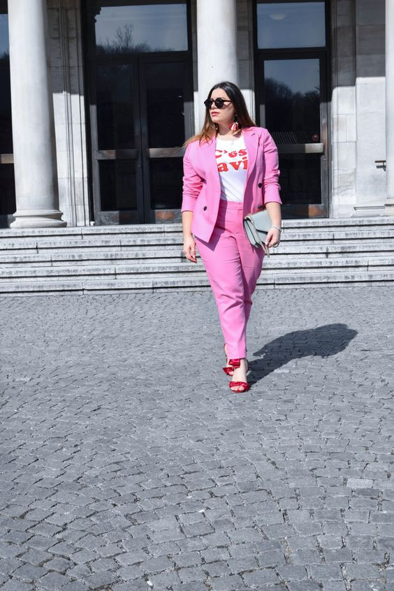a hot pink pantsuit, a printed tee, red heels and a grey bag will give your look an edge