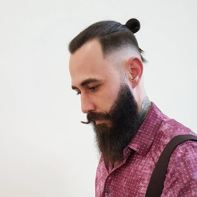 a samurai bun and a low fade goes down low and a full beard finishes off the look