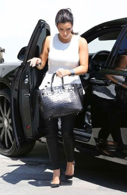 Kim Kardashian rocking black leather leggings, a white peplum top, black heels and a black crocodile leather bag