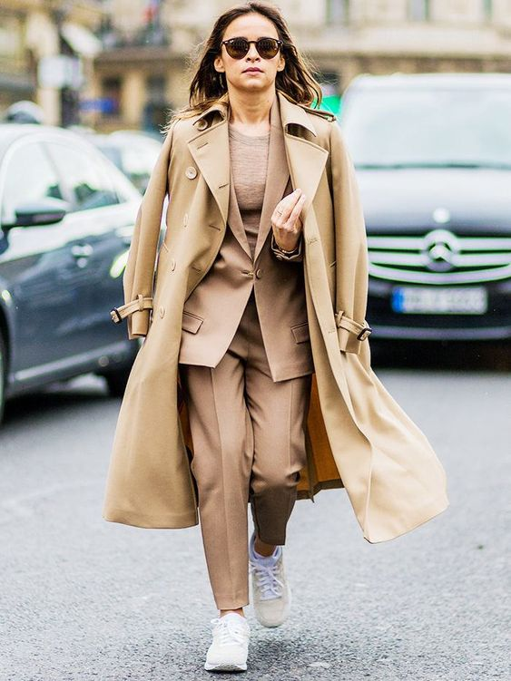 a beige suit and a top, white sneakers and a camel coat on top