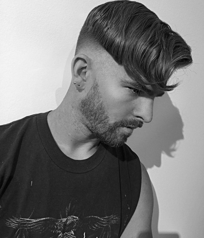 a undercut with thick wavy hair looks neat on top and bold thanks to the fade
