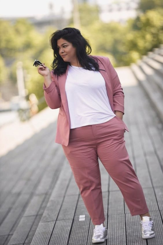 a dusty pink pantsuit with a white tee and silver sneakers is a cool look with a casual feel