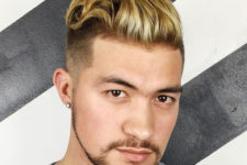 16 long textured slicked back hair with a high fade is accented with blonde highlights