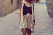 With beige dress, black vest and ankle boots
